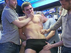 Horny men take down a cocky hustler at a busy sex arcade