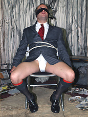 Gay stud gets tied to a chair and sucks the cock of a well dressed gay hunk