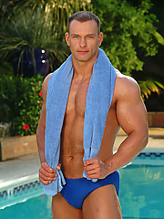 Muscle man shows his perfect body by the pool