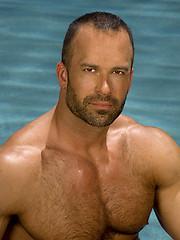 Big hairy bodybuilder posing by the pool
