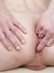 Sexy boy Julian Caro strokes his cock while fingering his ass.