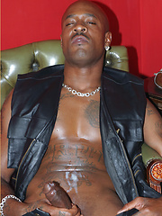 Gay black stallion wearing leather pulls his huge erection hard