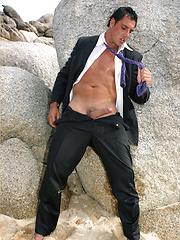 Marcello wearing a soaking wet business suit wanking on the rocks